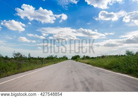 Driving On An Empty Road. Empty Asphalt Road Through The Green Field And Clouds On Blue Sky In Summe