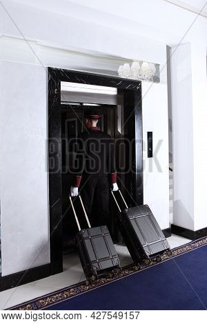 Doorman Carries The Suitcases Into The Elevator. Hotel Service. An Unrecognizable Person.the Concept