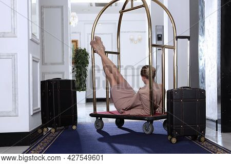 A Girl In A Pink Business Suit Lies In A Luggage Trolley At The Hotel. Slender Female Legs. Fashiona