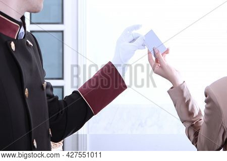 A Girl In A Pink Business Suit Gives The Doorman A Key Card. Doorman In Uniform. Unrecognizable Peop