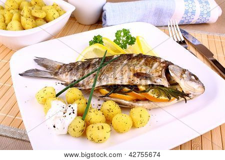 Whole Grilled Fish Served With Potatoes, Lemon And Sauce