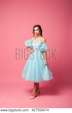 A Young Woman In An Airy Dress With Sleeves And Beige Shoes Poses Against An Isolated Background. A