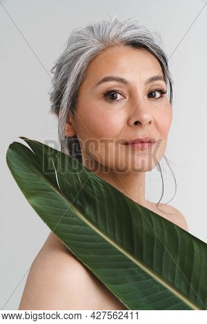 Mature shirtless woman with grey hair posing with green leaf isolated over white background
