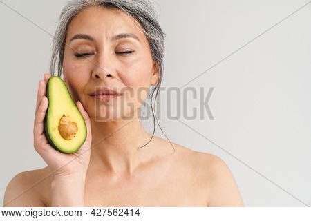 Mature shirtless woman with grey hair showing avocado isolated over white background