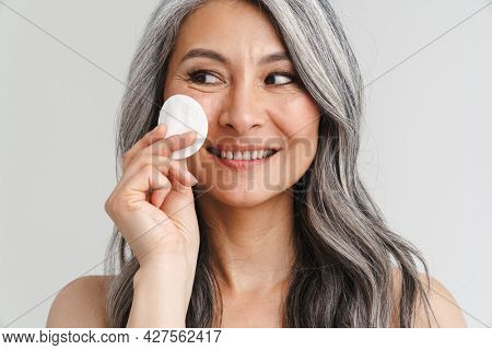 Mature shirtless woman with grey hair using cotton pad isolated over white background