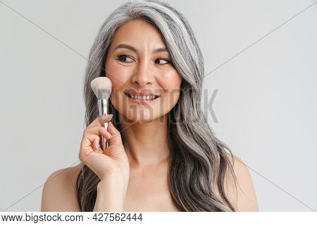 Mature shirtless woman with grey hair using powder brush isolated over white background