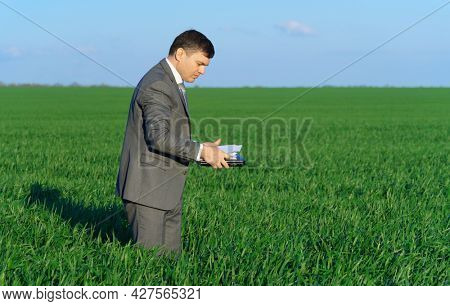 businessman works in a green field, freelance and business concept, green grass and blue sky as background