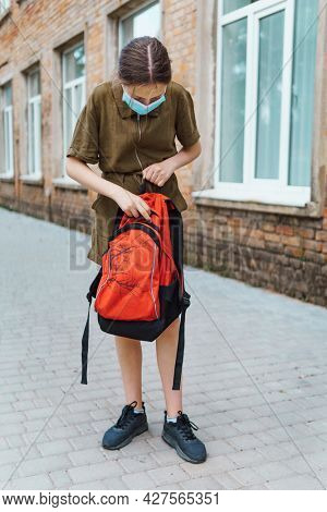 teen schoolgirl on the way to the school, she get books out of a backpack, they use protective face masks to protect against virus, coronavirus infection, education and back to school concept