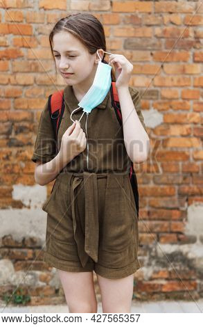 schoolgirl poses against a brick wall in the backyard of the school, wearing a protective mask on her face from a coronavirus infection, education and back to school concept