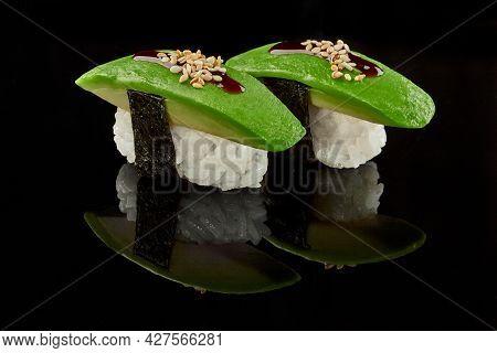 Two Nigirizushi With Avocado, Unagi Sauce And Sesame