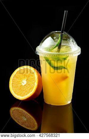Orange Juice In Takeaway Plastic Cup With Fresh Fruits On Dark Background