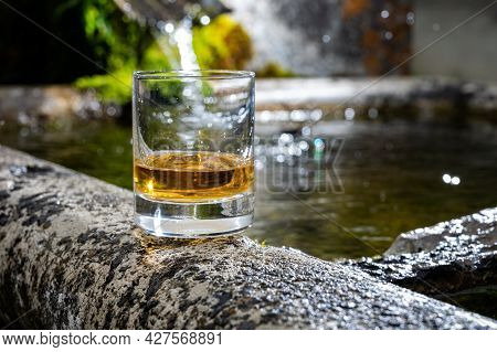 Glass Of Strong Scotch Single Malt Whisky Served On Old Stone Reservoir For Water From Mountain Spri