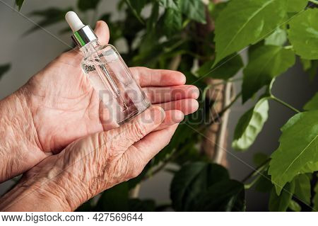 Serum In Wrinkled Hands And Copy Space. Skincare, Anti-aging Cosmetics, Healthcare Concept. Top View