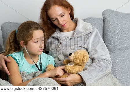 Mom Looking Lovingly At Her Daughter. Mother And Child Playing Doctor And Patient Sitting Together O