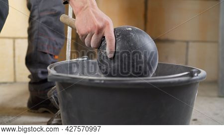 Worker Mixes The Mortar. Workers Hands Mixing Grout For Filling Space Between Ceramic Tiles. A Worke