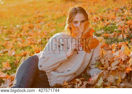 Woman Hide Her Face With Yellow Autumnal Leaf. Happy Beautiful Girl Have A Good Time Resting In A Au