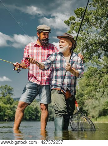 Grandfather And Boy Fishing Together. Happy Father And Son Fishing In River Holding Fishing Rods. Br