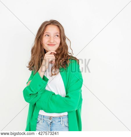 Cut young female girl with happy smile, looking away, standing against white background in green shirt. Portrait of fun teen student Studio Shot