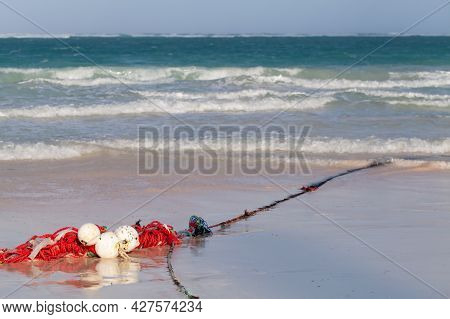 Red White Floats On A Rope Lay Over Wet Sandy Coast Of Bavaro Beach, Dominican Republic