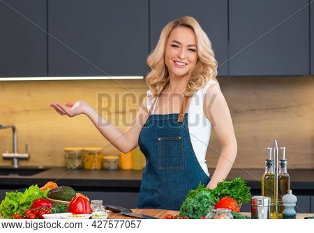 Young woman prepares food and hosts a cooking show. The blogger streams from modern kitchen. Vegetarian healthy food preparation.