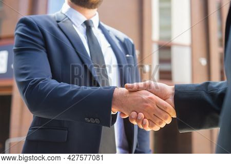 Handshake close-up. Businessman and his colleague are shaking hands in front of modern office building. Financial investors outdoor. Banking and business.