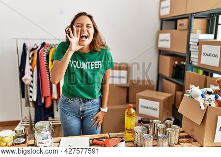 Beautiful hispanic woman wearing volunteer t shirt at donations stand shouting and screaming loud to side with hand on mouth. communication concept.