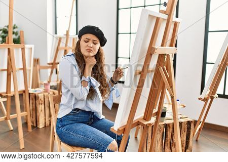 Young hispanic artist woman painting on canvas at art studio touching painful neck, sore throat for flu, clod and infection