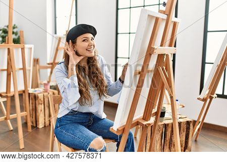 Young hispanic artist woman painting on canvas at art studio smiling with hand over ear listening an hearing to rumor or gossip. deafness concept.