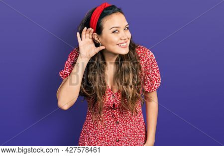 Young hispanic girl wearing casual clothes smiling with hand over ear listening an hearing to rumor or gossip. deafness concept.