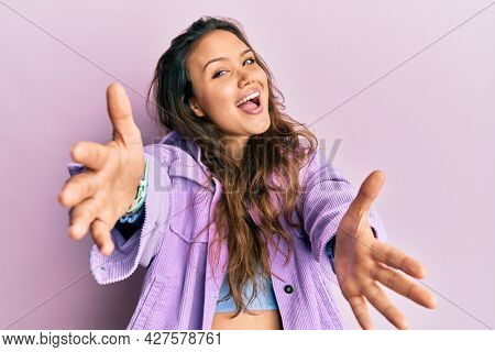 Young hispanic girl wearing casual clothes looking at the camera smiling with open arms for hug. cheerful expression embracing happiness.