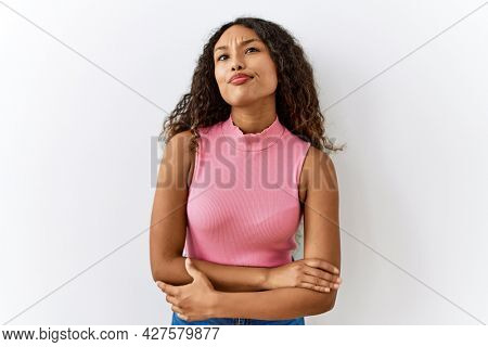 Beautiful hispanic woman standing over isolated background smiling looking to the side and staring away thinking.
