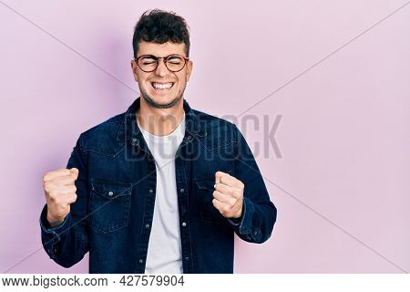 Young hispanic man wearing casual clothes and glasses excited for success with arms raised and eyes closed celebrating victory smiling. winner concept.