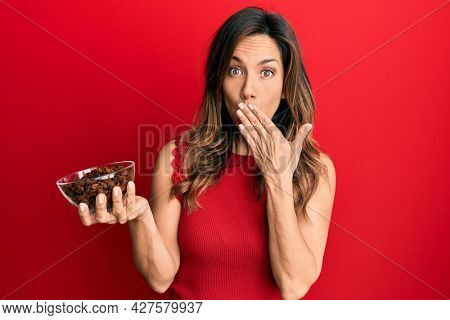 Young latin woman holding bowl with raisins covering mouth with hand, shocked and afraid for mistake. surprised expression