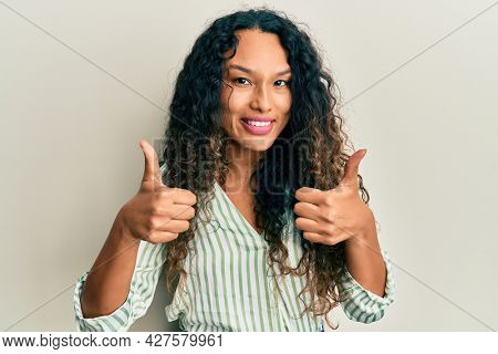 Young latin woman wearing casual clothes success sign doing positive gesture with hand, thumbs up smiling and happy. cheerful expression and winner gesture.