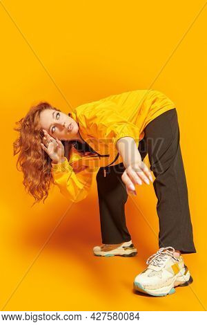 Full length portrait of a stylish girl in yellow hoodie posing at studio on a yellow background. Youth style. Modern hip-hop dancer.