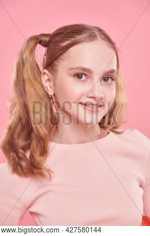 Portrait of a pretty teenage girl in light summer clothes and with funny ponytails smiling at camera. Teenage style.