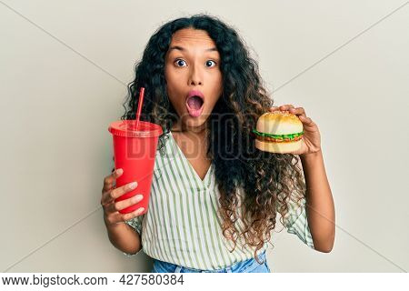 Young latin woman eating a tasty classic burger and soda afraid and shocked with surprise and amazed expression, fear and excited face.