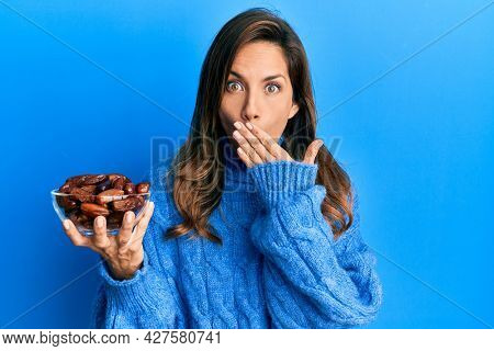 Young latin woman holding bowl with dates covering mouth with hand, shocked and afraid for mistake. surprised expression