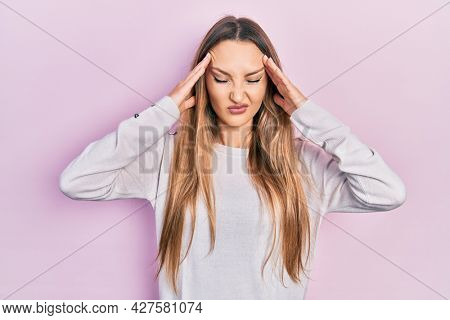 Young blonde girl wearing casual clothes with hand on head, headache because stress. suffering migraine.