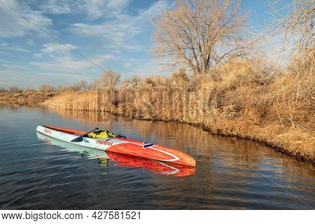 Fort Collins, CO, USA - March 15, 2020: A long racing flatwater stand up paddleboard (Mistral Stealth) on a calm lake after paddling workout in early spring - recreation, training and fitness concept.