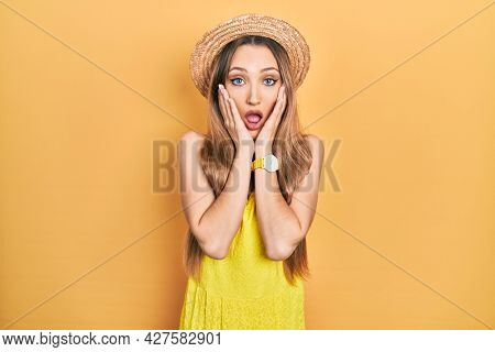 Young blonde girl wearing summer hat afraid and shocked, surprise and amazed expression with hands on face