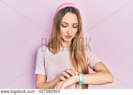 Young blonde girl wearing casual clothes checking the time on wrist watch, relaxed and confident