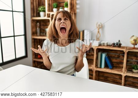 Young caucasian girl wearing casual clothes sitting on the table at home crazy and mad shouting and yelling with aggressive expression and arms raised. frustration concept.