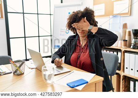 African american woman with afro hair working at the office wearing operator headset covering eyes with hand, looking serious and sad. sightless, hiding and rejection concept