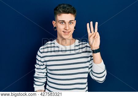 Young caucasian boy with ears dilation wearing casual striped shirt showing and pointing up with fingers number three while smiling confident and happy.