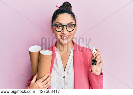 Beautiful middle eastern woman holding paper blueprints and house keys smiling with a happy and cool smile on face. showing teeth.