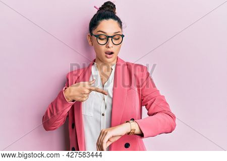 Beautiful middle eastern woman wearing business jacket and glasses in hurry pointing to watch time, impatience, upset and angry for deadline delay