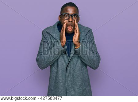 Young african american man wearing business clothes and glasses afraid and shocked, surprise and amazed expression with hands on face