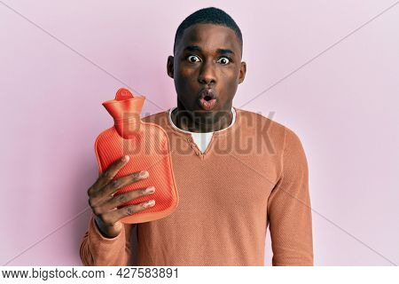 Young african american man holding heat water bag scared and amazed with open mouth for surprise, disbelief face