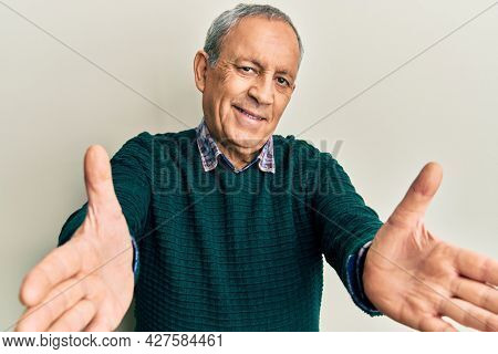 Handsome senior man with grey hair wearing casual sweater looking at the camera smiling with open arms for hug. cheerful expression embracing happiness.